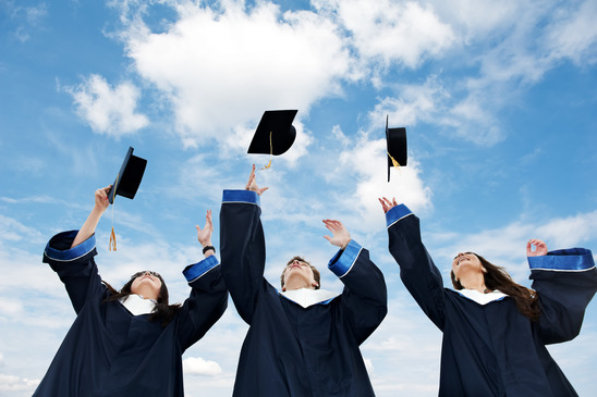 three high school graduating teens tossing caps on to the sky